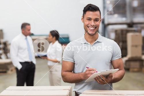 Manager looking at camera while holding clipboard