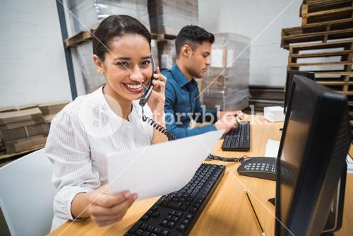Smiling manager on the phone holding a document