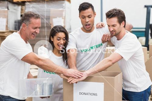 Volunteer team holding hands on a box of donations