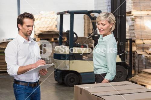 Two warehouse managers checking inventory