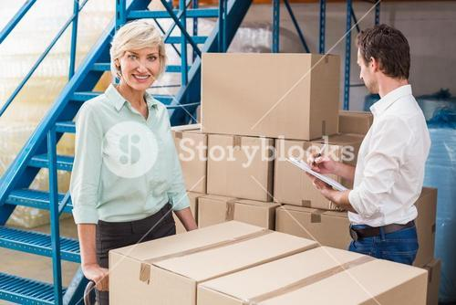 Focused warehouse managers with clipboard