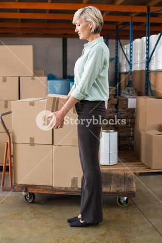 Warehouse manager holding cardboard box