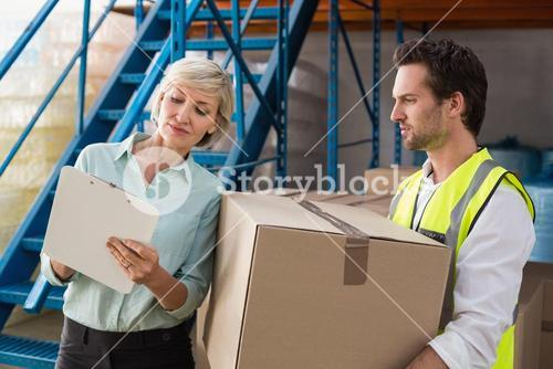 Warehouse manager and worker looking at clipboard