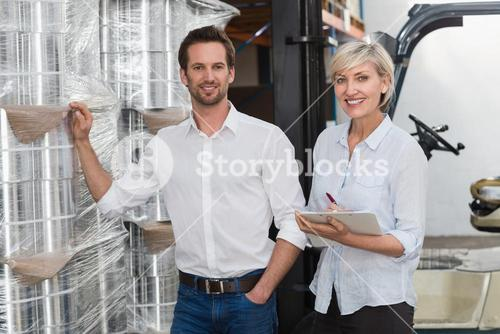 Smiling warehouse managers checking inventory