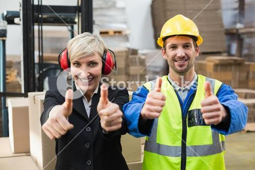 Warehouse worker and his manager giving thumbs up
