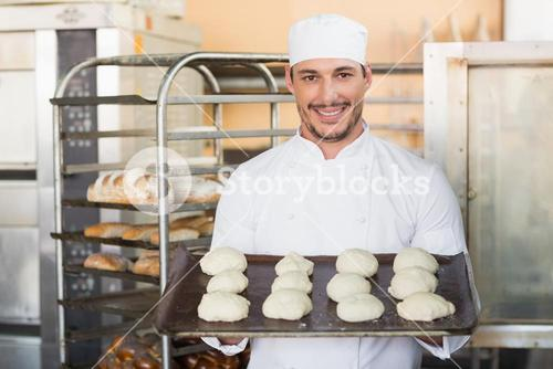 Smiling baker holding tray of raw dough