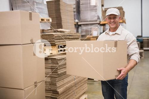 Portrait of worker carrying box