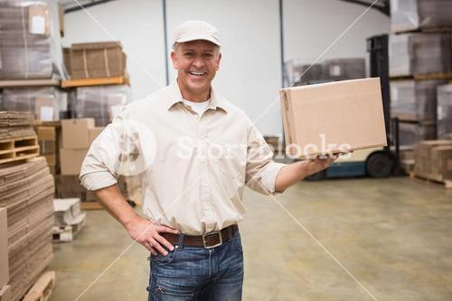 Smiling worker holding cardboard box