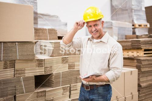 Smiling warehouse worker with clipboard