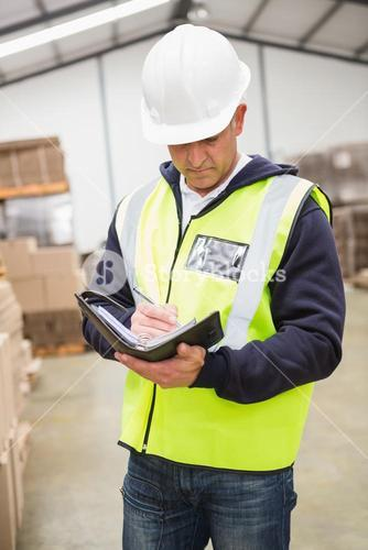 Serious warehouse worker with diary