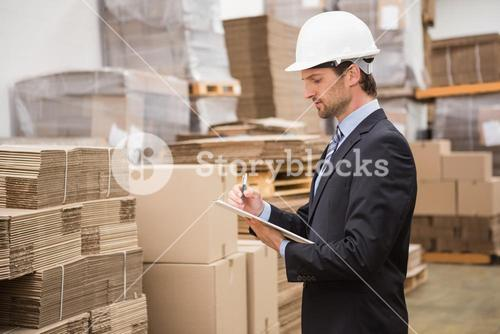 Serious warehouse manager checking inventory