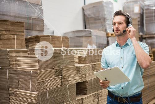 Warehouse worker wearing a headset holding clipboard