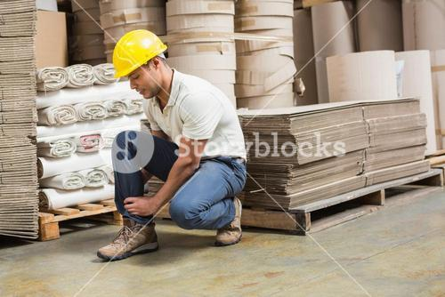 Worker with sprained ankle on the floor