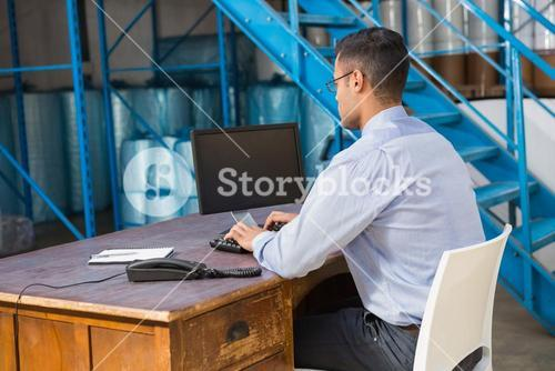 Warehouse manager working on computer
