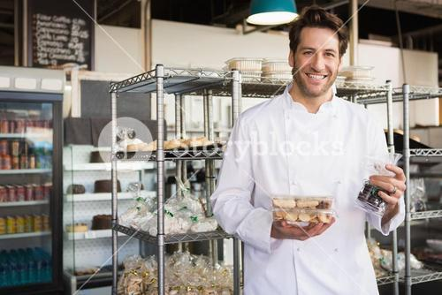 Cheerful baker holding coffee house and food