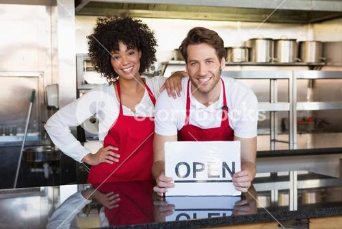 Happy colleagues posing with open sign