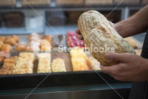 Worker in apron holding fresh loaf