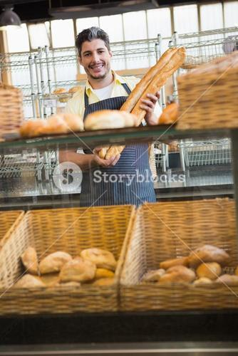 Smiling waiter holding two baguettes