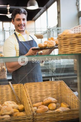 Smiling waiter showing tray of breads