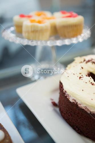 Display case of cupcakes and sweet cake