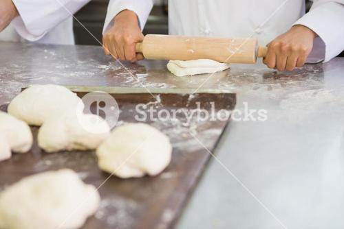 Baker kneading dough with rolling pin