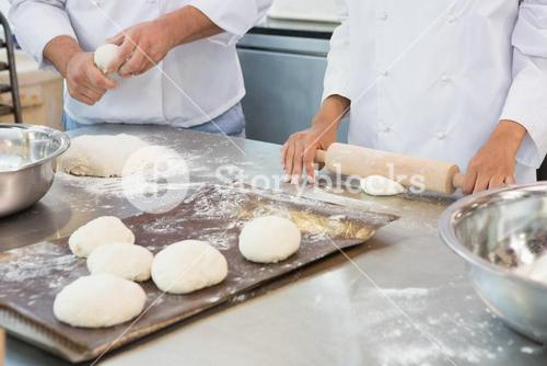 Co-workers kneading uncooked dough together