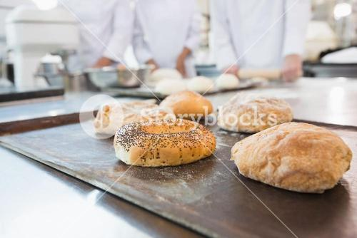 Co-workers making bagels and bread together