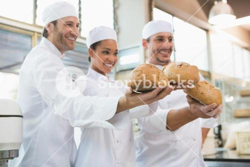 Smiling colleagues showing loaf of bread