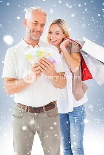Happy couple with shopping bags and cash