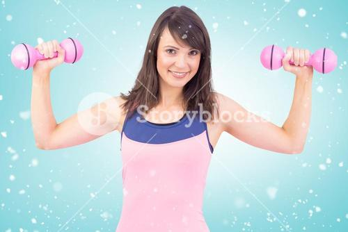 Composite image of smiling woman holding hand weight