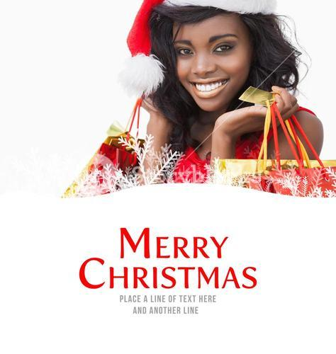 Composite image of festive woman standing looking while holding bags