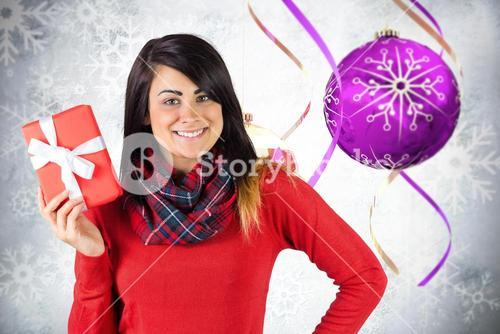 Composite image of happy brunette showing a gift