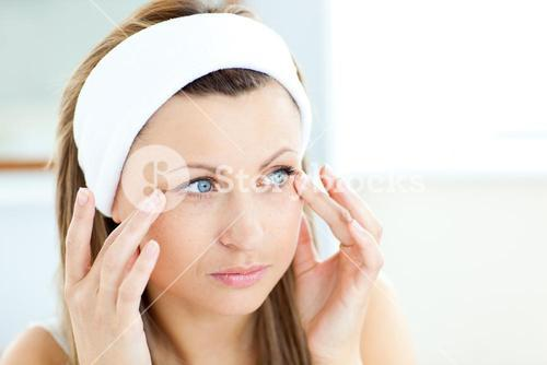 Young woman putting cream on her face wearing a headband in the bathroom