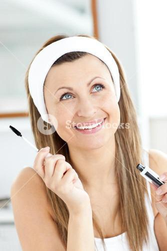 Jolly young woman using mascara in the bathroom