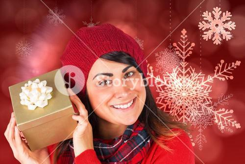 Composite image of pretty brunette in hat holding a gift