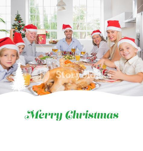 Composite image of smiling family around the dinner table at christmas