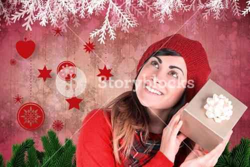 Composite image of brunette in hat listening a gift