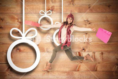 Composite image of happy brunette jumping with gifts bags