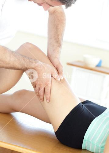 Young woman receiving a leg massage in a health club