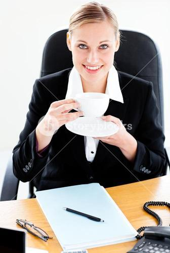 Radiant businesswoman holding a coffee sitting at her desk