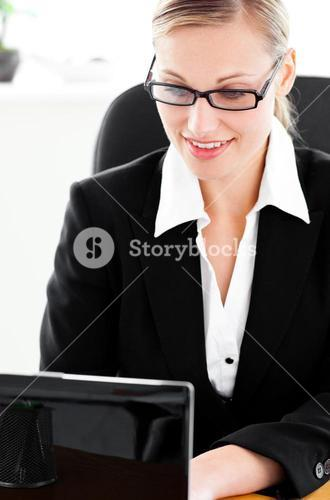 Busy young businesswoman using her laptop sitting at her desk