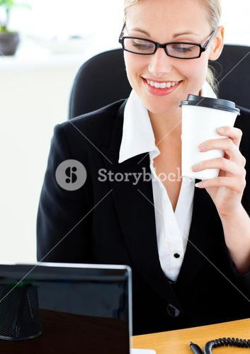 Radiant businesswoman holding a coffee using her laptop sitting at her desk