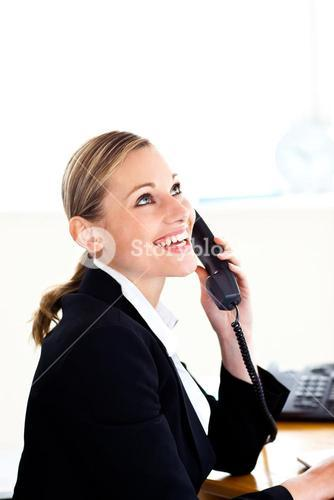Bright businesswoman talking on phone in her office