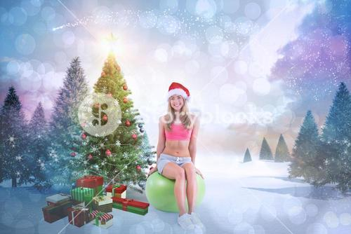 Composite image of festive fit blonde sitting on exercise ball