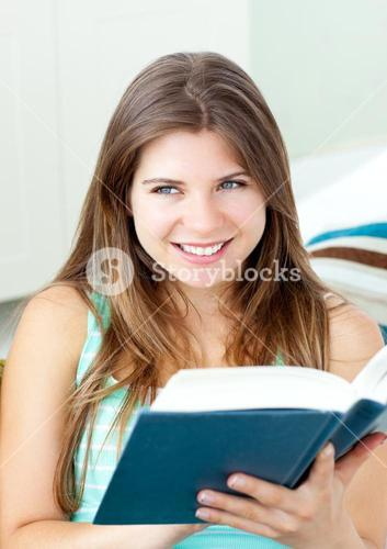 Bright woman reading a book sitting on a sofa