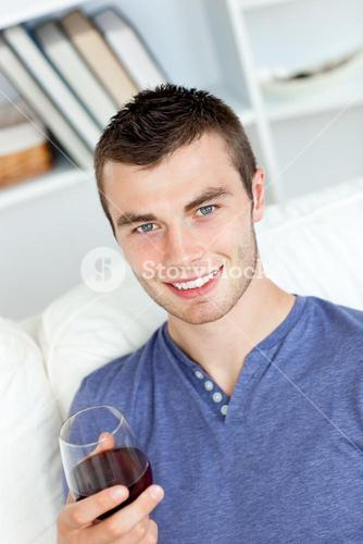 Charismatic young man holding a glass of wine sitting on a sofa in the livingroom