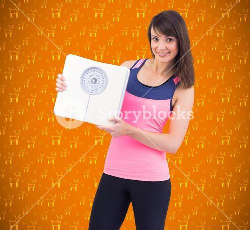 Composite image of smiling woman holding weighing scales