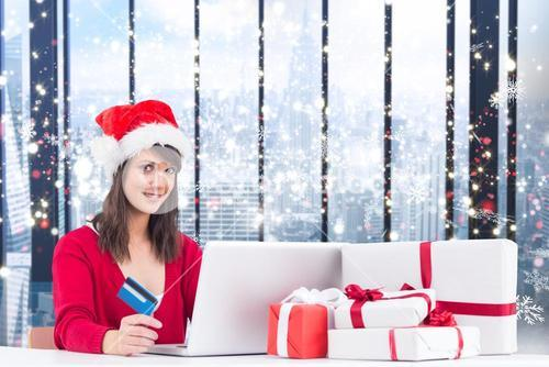 Composite image of festive brunette shopping online with laptop