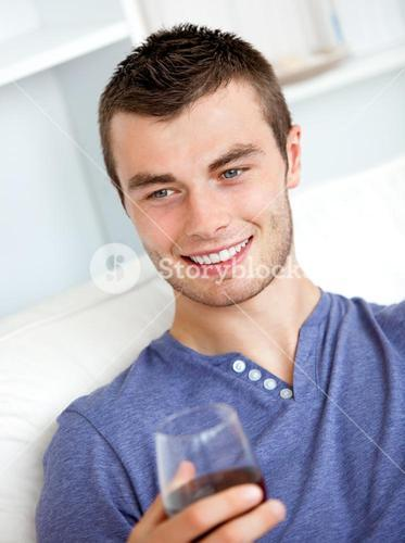 Handsome young man holding a glass of wine sitting on a sofa in the livingroom
