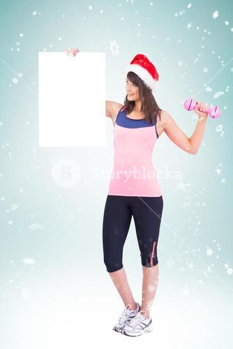 Composite image of festive fit brunette holding poster with dumbbell